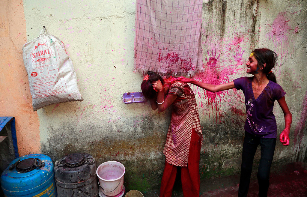 . An Indian girl splatters the back of another with colored water as they celebrate Holi, the Hindu festival of colors, in Mumbai India, Monday, March 17, 2014. The festival heralds the arrival of spring. (AP Photo/Rafiq Maqbool)