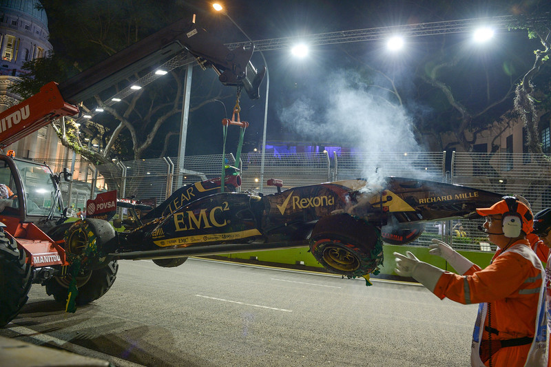 . Track Marshals recover the crashed car belonging to Lotus driver Pastor Maldonado of Venezuela during the second practice session of the Formula One Singapore Grand Prix night race on September 19, 2014.MOHD RASFAN/AFP/Getty Images