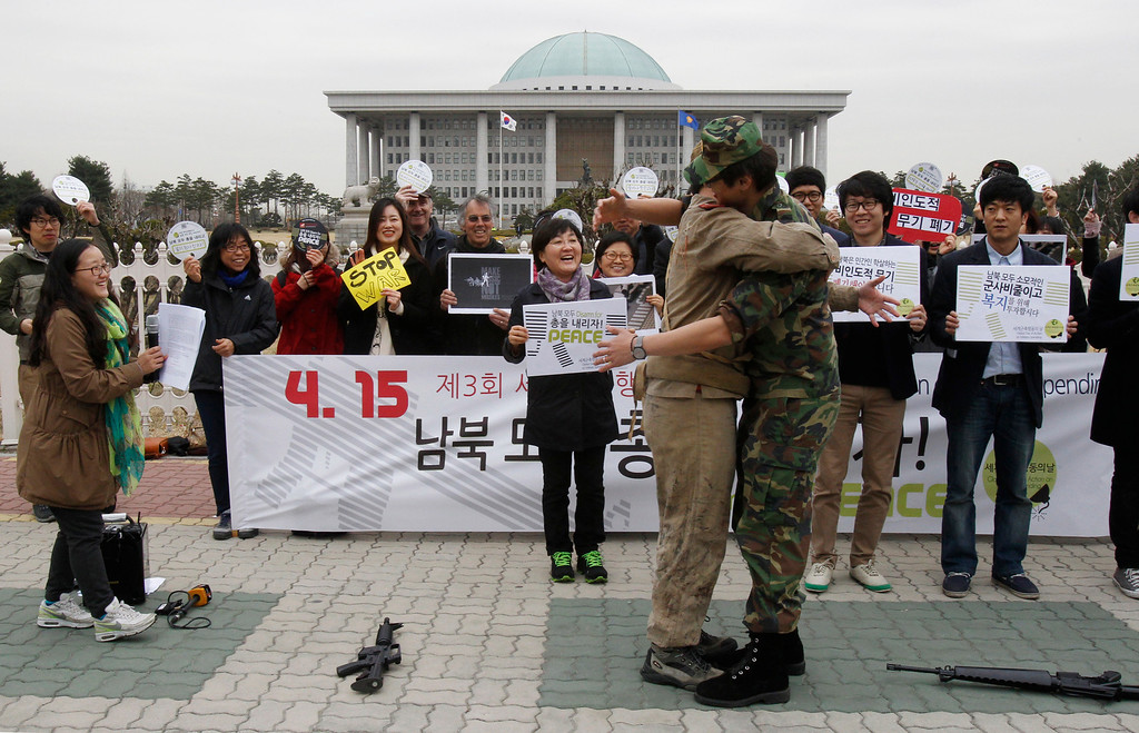 . Anti-war activists wearing military clothes of a North, left, and South Korea hug each other during a rally to mark Global Day of Action on Military Spending in front of the National Assembly in Seoul, South Korea, Monday, April 15, 2013. They demanded peaceful unification of the Korean peninsula. (AP Photo/Ahn Young-joon)