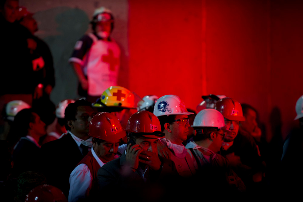 Description of . Employees and rescue workers listen as the Minister of the Interior, Miguel Angel Osorio Chong (out of frame) addresses a press conference at the headquarters of state-owned Mexican oil giant Pemex in Mexico City on January 31, 2013, following a blast inside the building. An explosion rocked the skyscraper, leaving up to 25 dead and 101 injured, as a plume of black smoke billowed from the 54-floor tower, according to official sources. AFP PHOTO / YURI  CORTEZ/AFP/Getty Images