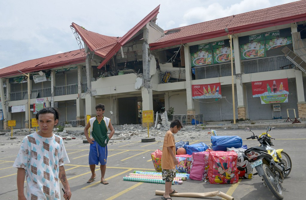 . People stand in front of a damaged public market on the popular tourist island of Bohol, central Philippines on October 16, 2013 following a 7.1-magnitude earthquake in the area on October 15.  AFP PHOTO / Jay DIRECTO/AFP/Getty Images