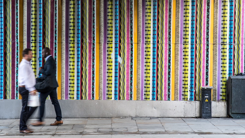 Pedestrians passing colourful striped wall