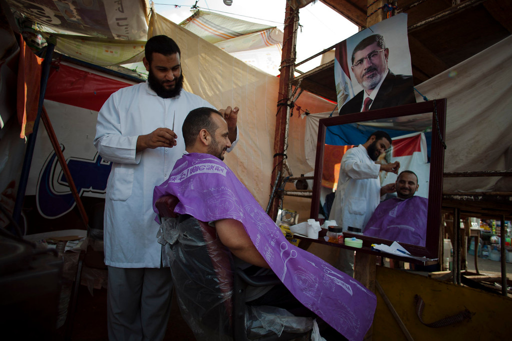 . A supporter of Egypt\'s ousted President Mohammed Morsi gets his hair cut in a tent outside Rabaah al-Adawiya mosque, where protesters have installed a camp and held daily rallies at Nasr City, Cairo, Egypt, Tuesday, Aug. 13, 2013. Instead of rushing for the exits, Islamist supporters of Egypt\'s ousted president are replacing tents with wooden huts in their sprawling Cairo encampment. Barbershops have sprung up and many tents now have satellite dishes. (AP Photo/Khalil Hamra)