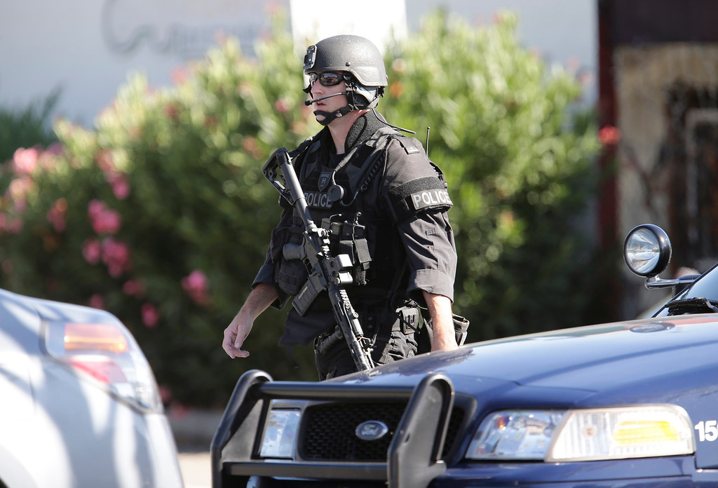 . A member of the San Jose Police Depart MERGE unit  prepares to search the neighborhood at Diana Lane and Story Rd. for a gunman who tried to rob a check-cashing store in East San Jose, Calif. on Thursday, Aug. 1, 2013.  (Gary Reyes/Bay Area News Group)