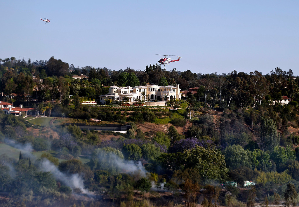 . Smoke rises as firefighters work in the brush as two fire fighting helicopters pass  each other above one of the colossal homes of Fairbanks Ranch where a wild fire threatened homes Tuesday, May 13, 2014, in San Diego.  (Wildfires pushed by gusty winds chewed through canyons parched by Californiaís drought, prompting evacuation orders for more than 20,000 homes on the outskirts of San Diego and another 1,200 homes and businesses in Santa Barbara County 250 miles to the north.  (AP Photo)