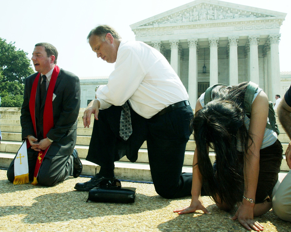 . WASHINGTON - JUNE 26:  (L-R) Rev. Rob Schenck of the National Clergy Council, Pastor Ken Wilde of the National Prayer Center and Yuko Takatsubaki of Portland Bible College in Portland, Oregon, pray outside the U.S. Supreme Court after a ruling on homosexual and privacy rights June 26, 2003 in Washington, DC. The U.S. Supreme Court ruled that states cannot ban sodomy between consenting adults.    (Photo by Alex Wong/Getty Images)