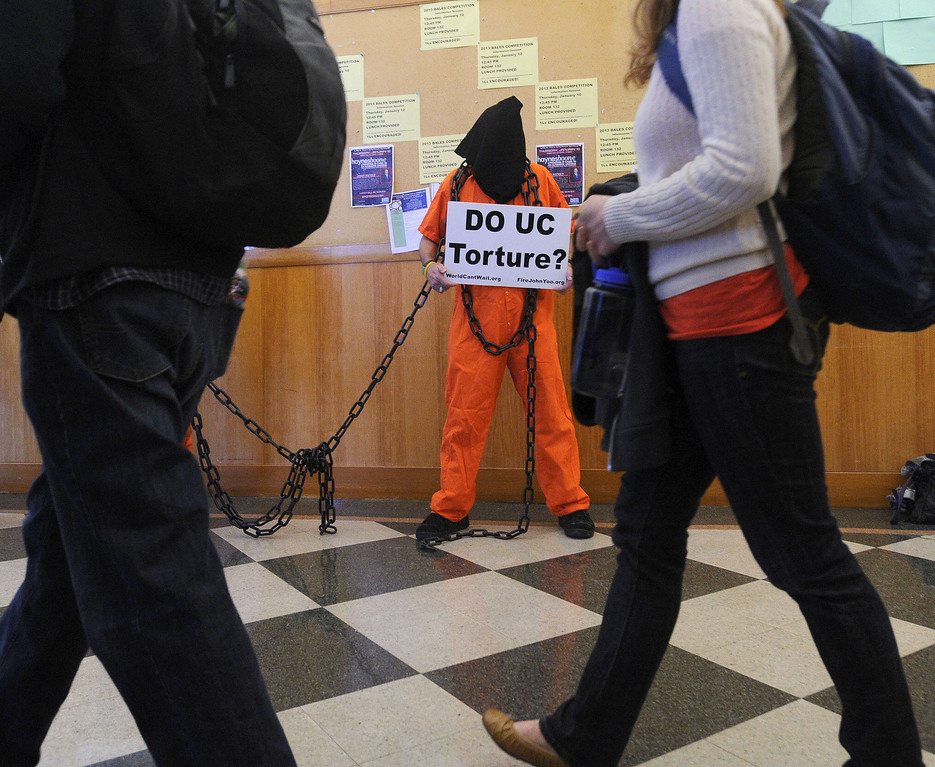 . Mike Baldwin, of Hayward and World Can\'t Wait, stands in protest as people enter an event involving UC Berkeley faculty member John Yoo held in Boalt Hall on the UC Berkeley campus in Berkeley, Calif. on Thursday, Jan. 10, 2013. Some feel that Yoo played a role in the torture program at the United States prison at Guantanamo under the Bush Administration and should not be employed by the university. The event was a debate on Obama Care with University of Saint Thomas School of Law Professor Michael Paulsen sponsored by the Berkeley Federalist Society. (Dan Honda/Staff)