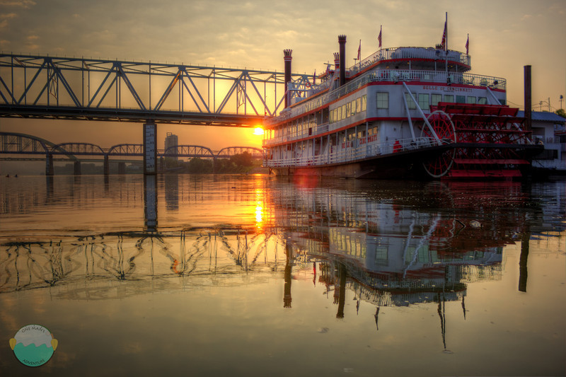 Riverboat Reflection<br /> The sun rising while the river is peaceful and calm showing off how reflections can b ein moving water.