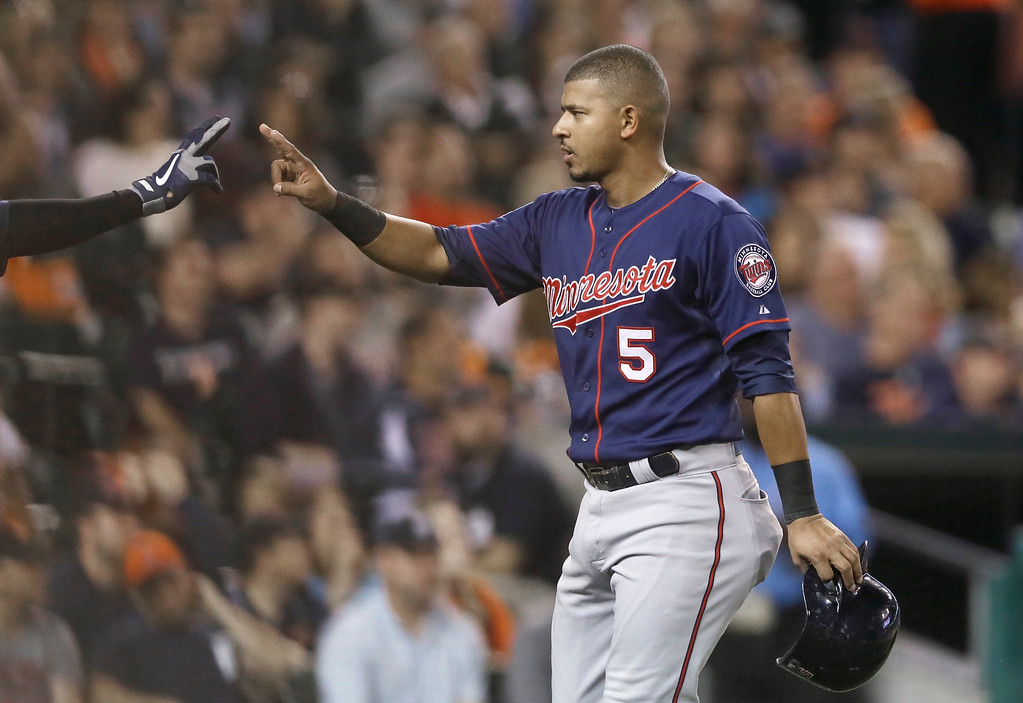 . Minnesota Twins\' Eduardo Escobar is congratulated after scoring on a single by teammate Brian Dozier during the fifth inning of a baseball game against the Detroit Tigers in Detroit, Saturday, Sept. 27, 2014. (AP Photo/Carlos Osorio)