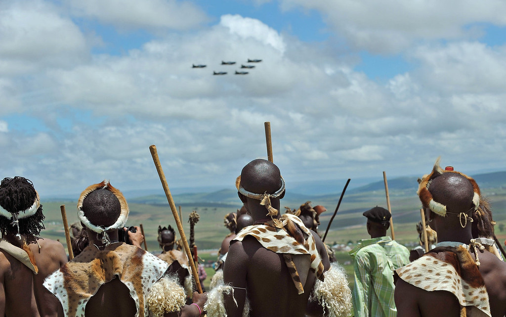 . A group of Zulu warriors, from KwaZulu Natal watch a fly past from near a public viewing tent during the burial of former South African president Nelson Mandela in Qunu, South Africa, Sunday, Dec. 15, 2013. (AP Photo/Antoine de Ras)