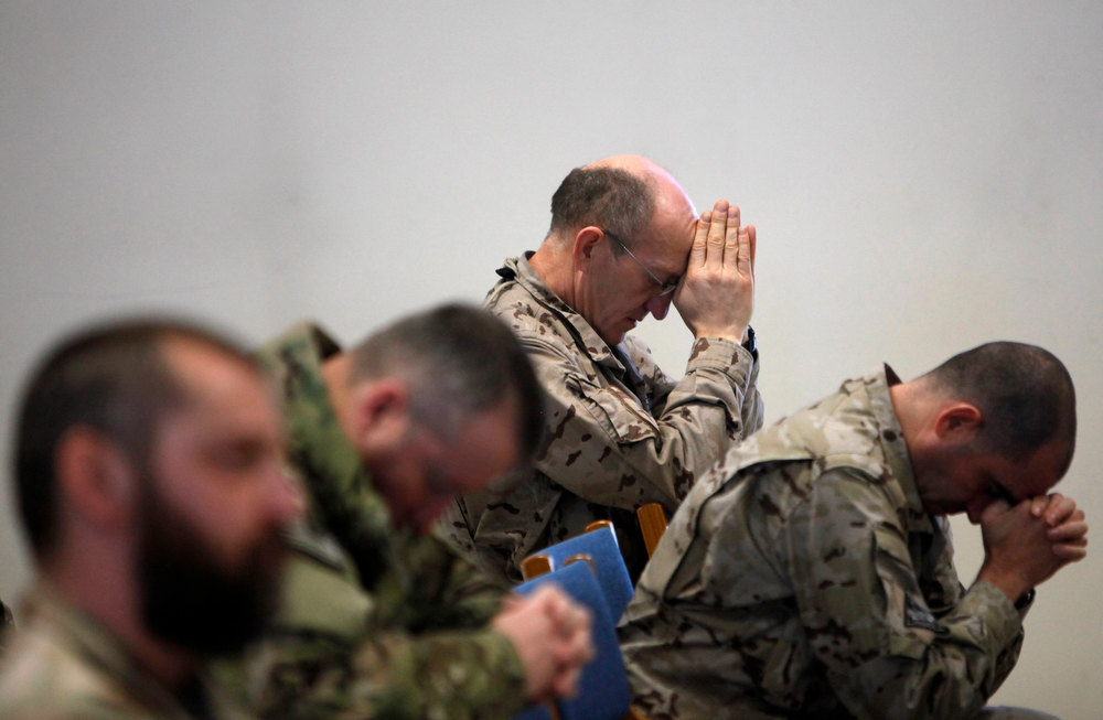 Description of . NATO troops from the International Security Assistance Force (ISAF) prays during Christmas celebrations in Kabul December 25, 2012. REUTERS/Mohammad Ismail