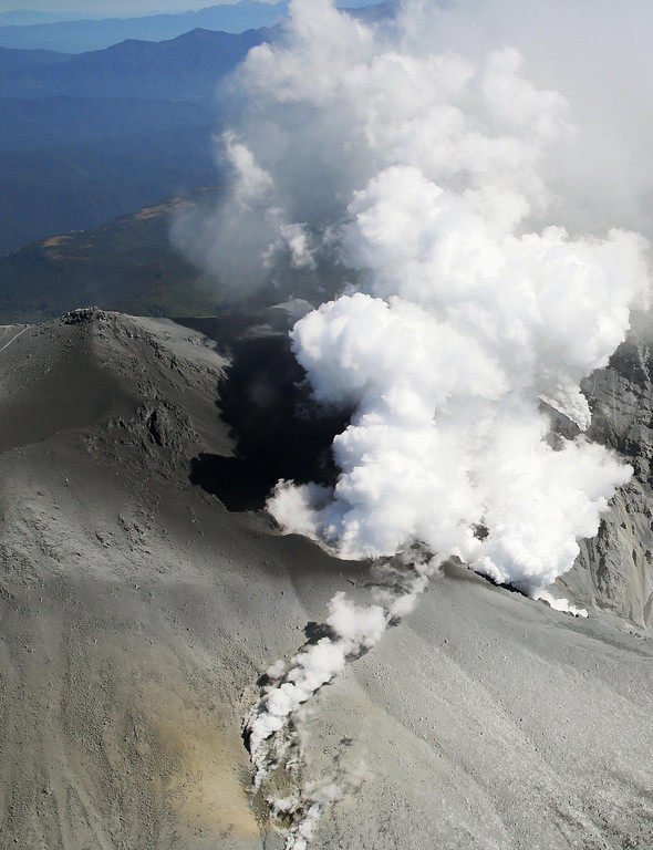 . Dense white plumes of gases and ash are spewed out from the summit crater of Mount Ontake, central Japan, Monday afternoon, Sept. 29, 2014. Japanese soldiers managed to bring down eight more bodies by helicopter from the ash-blanketed peak of a still-erupting volcano on Monday, before toxic gases and ash forced them to suspend the recovery effort in the early afternoon. (AP Photo/Kyodo News)