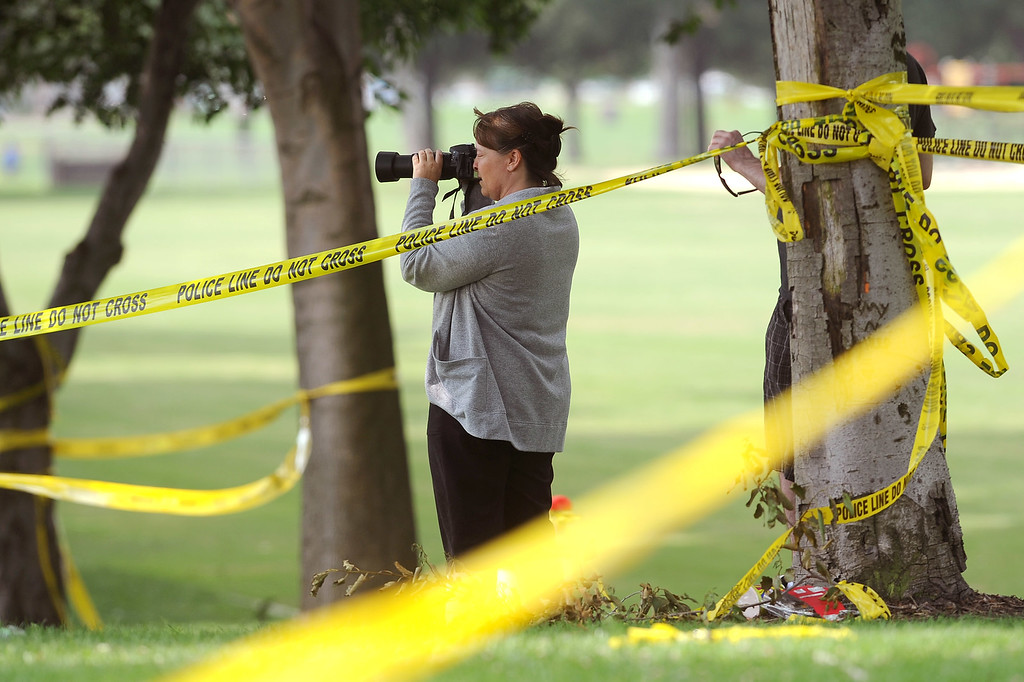 . A passerby snaps a picture of the scene after a Fourth of July fireworks show mishap at Rancho Santa Susana Community Park in Simi Valley, CA July 5, 2013.   The accident injured 28 onlookers Thursday night. (Andy Holzman/Los Angeles Daily News)