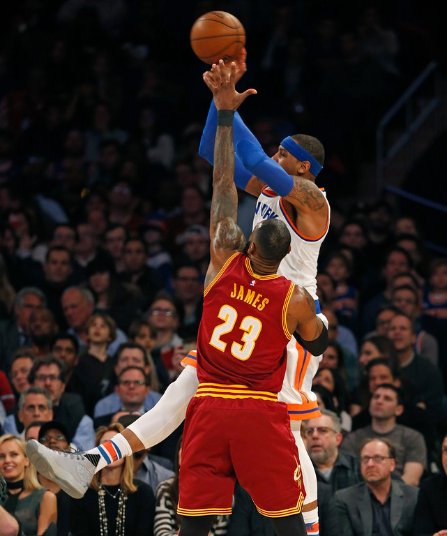 . New York Knicks forward Carmelo Anthony (7) passes after realizing he has not shot with Cleveland Cavaliers forward LeBron James (23) defending in the first quarter of an NBA basketball game at Madison Square Garden in New York, Wednesday, Dec. 7, 2016. (AP Photo/Kathy Willens)