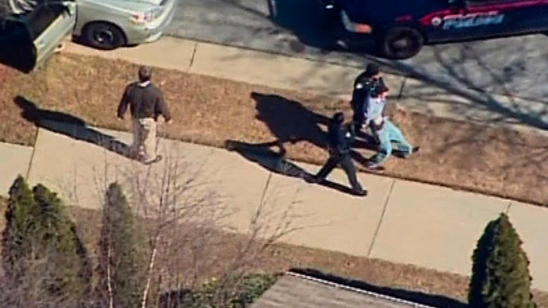 . A male suspect is escorted to a police cruiser in this still image taken from video at Price Middle School in Atlanta, Georgia January 31, 2013.  A 14-year old student was wounded on Thursday in a shooting outside the school according to police reports.  REUTERS/WXIA-TV/NBC/Handout