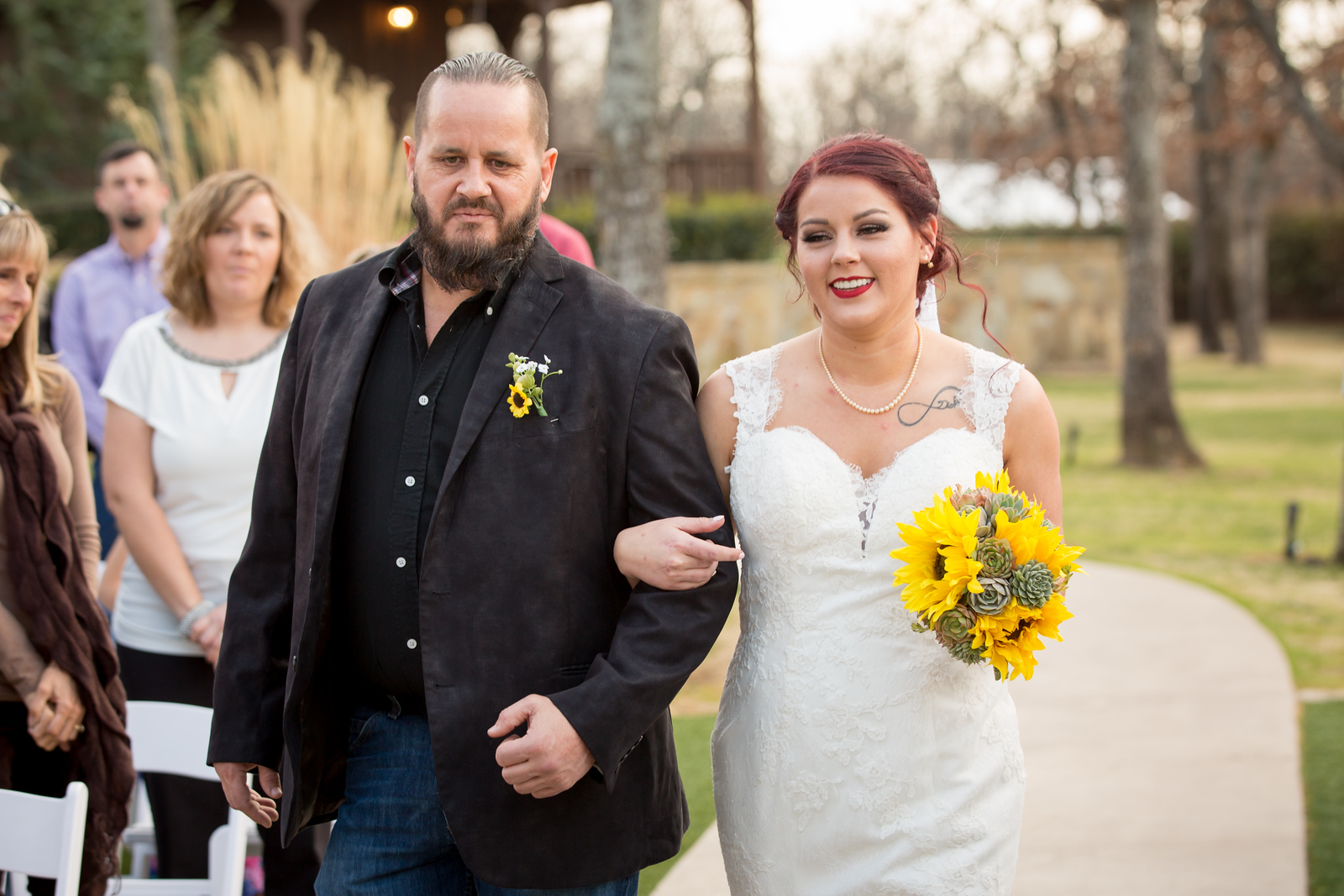 a bride being walked down the aisle of her wedding ceremony holding a yellow bouquet