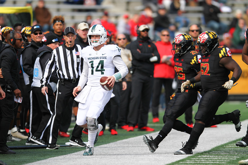 Maryland DB #25 Antoine Brooks Jr. and DL #52 Oluwaseun Oluwatimi run Michigan State QB #14 Brian Lewerke out of bounds