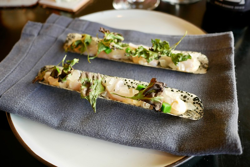 Kødbyens Fiskebar: Atlantic Ocean razor clam with grilled parsley, salsify & pickled green tomato in edible shells colored with squid ink