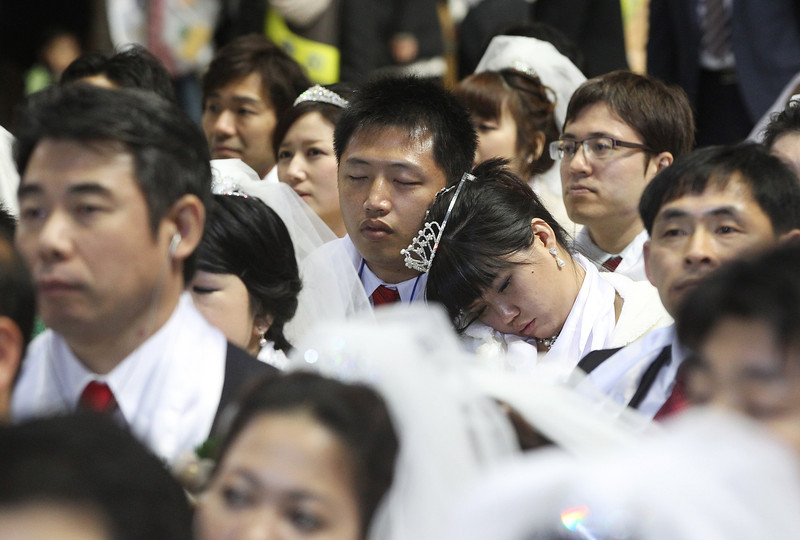 . A newly-married couple takes a nap in a mass wedding ceremony at the CheongShim Peace World Center in Gapyeong, South Korea, Wednesday, Feb. 12, 2014. Some 2,500 South Korean and foreign couples exchanged or reaffirmed marriage vows in the Unification Church\'s mass wedding arranged by Hak Ja Han Moon, wife of the late Rev. Sun Myung Moon, the controversial founder of the Unification Church. (AP Photo/Lee Jin-man)
