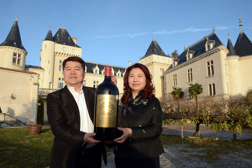 . Chinese billionaire Lam Kok (L) and his spouse pose for a photograph on December 20, 2013, in front of the Chateau de La Riviere, in La Riviere. This photograph was taken less than an hour before the crash.  AFP PHOTO / MEHDI FEDOUACH/AFP/Getty Images