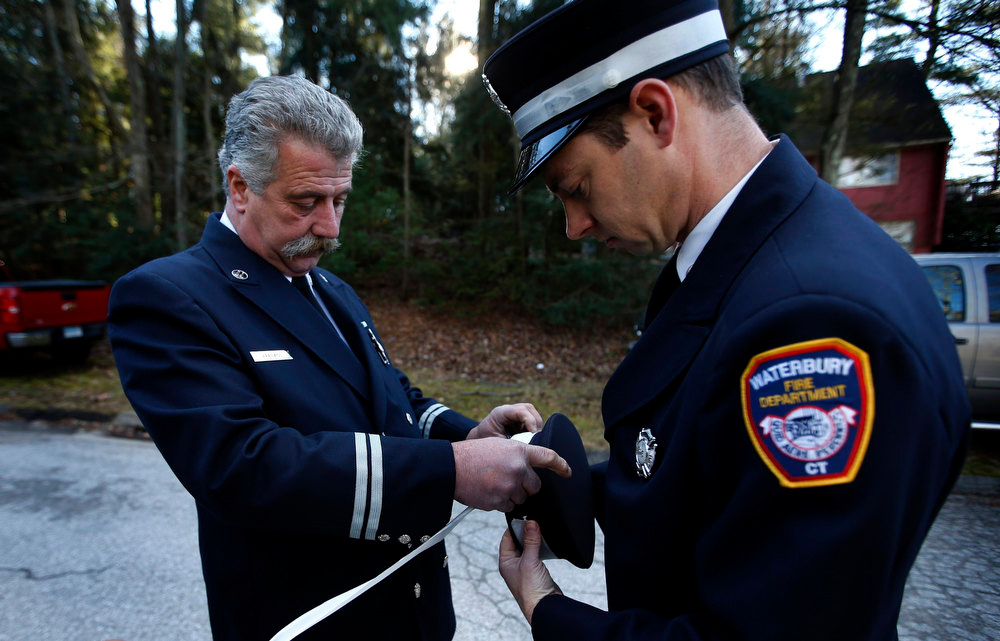 Description of . Waterbury Connecticut firefighters Gary Leblanc (L) and Dave Morgan tie white ribbons to their hats outside the Saint Rose of Lima Parish cemetery before the burial service of seven-year-old Daniel Barden, one of the 20 school children killed in the December 14 shootings at Sandy Hook Elementary School, in Newtown, Connecticut, December 19, 2012. Firefighters from around the region came to pay tribute to Barden, who had said he wanted to be a firefighter. REUTERS/Mike Segar