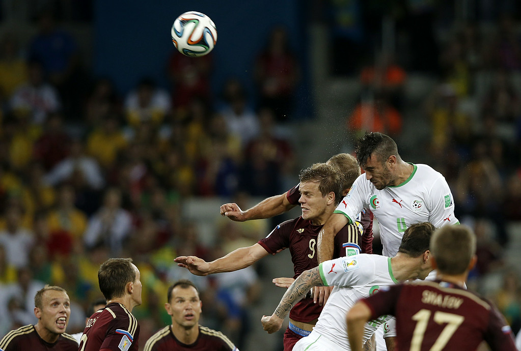 . Algeria\'s defender Essaid Belkalem (top R) heads the ball next to Russia\'s forward Alexander Kokorin (centre R) during a Group H football match between Algeria and Russia at the Baixada Arena in Curitiba during the 2014 FIFA World Cup on June 26, 2014. ADRIAN DENNIS/AFP/Getty Images