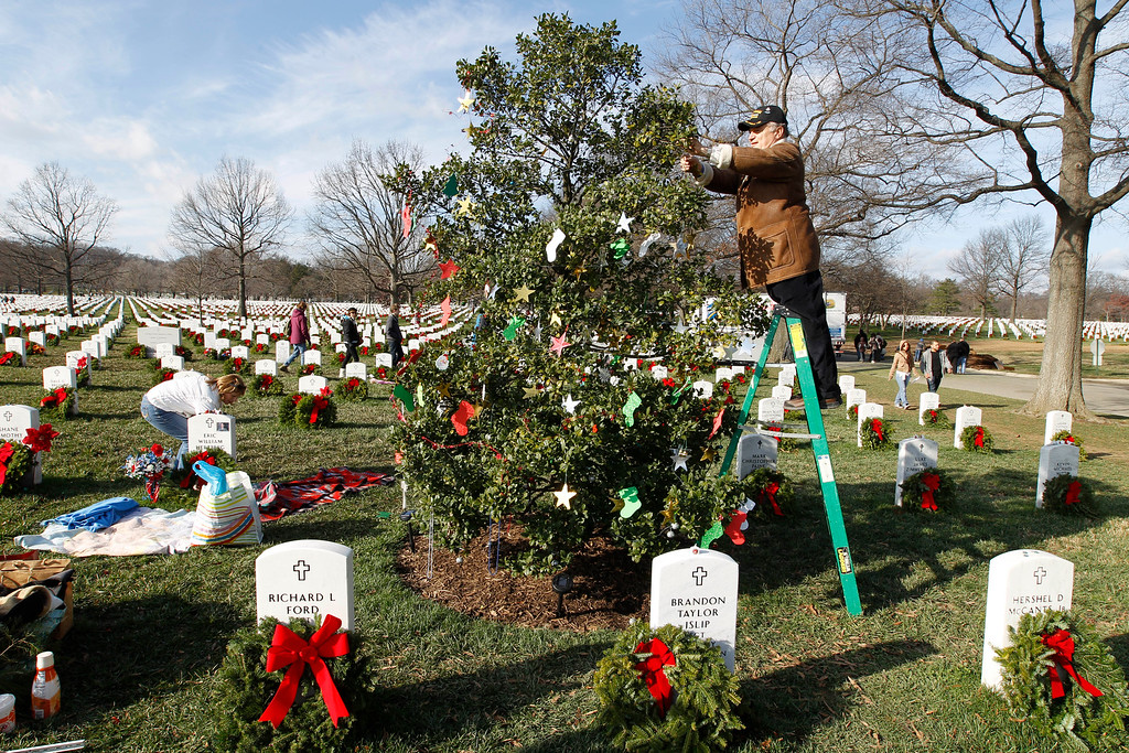 . William Duvel decorates a tree over the grave of his stepson Air Force Scott E. Duffman at Arlington National Cemetery in Washington Saturday Dec. 10, 2011, during Wreaths Across America Day. (AP Photo/Jose Luis Magana)