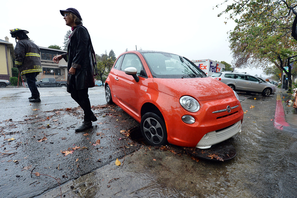 . Clair Hamner, of Oakland, stands near her car after getting stuck in a manhole on Grand Avenue in Oakland, Calif., on Thursday, Dec. 11, 2014. The manhole cover appeared to have been dislodged by the pressure from storm water rushing underground. (Kristopher Skinner/Bay Area News Group)
