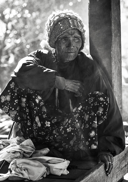 A woman from the Muun tribe sitting outside her home.  Chin State, Myanmar, 2017.