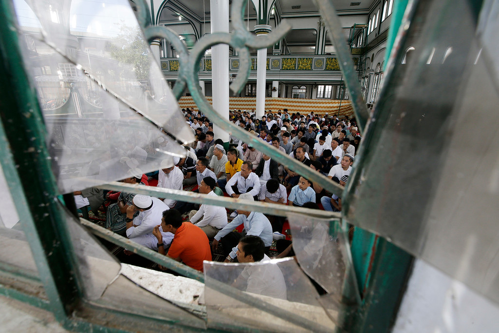 . Survivors are seen from a broken window as they hear Eid al-Fitr prayers inside the Saduc Grand Mosque, the biggest mosque that reopened near the former battle area between troops and Islamic extremists, to mark the end of the holy fasting month of Ramadan in Marawi city, southern Philippines, Friday, June 15, 2018. Thousands of displaced residents celebrated Eid al-Fitr inside emergency shelters and the threat of Islamic extremists and unexploded bombs lingers in the rubble after a disastrous five-month siege by Islamic State group-aligned fighters that began more than a year ago. (AP Photo/Aaron Favila)