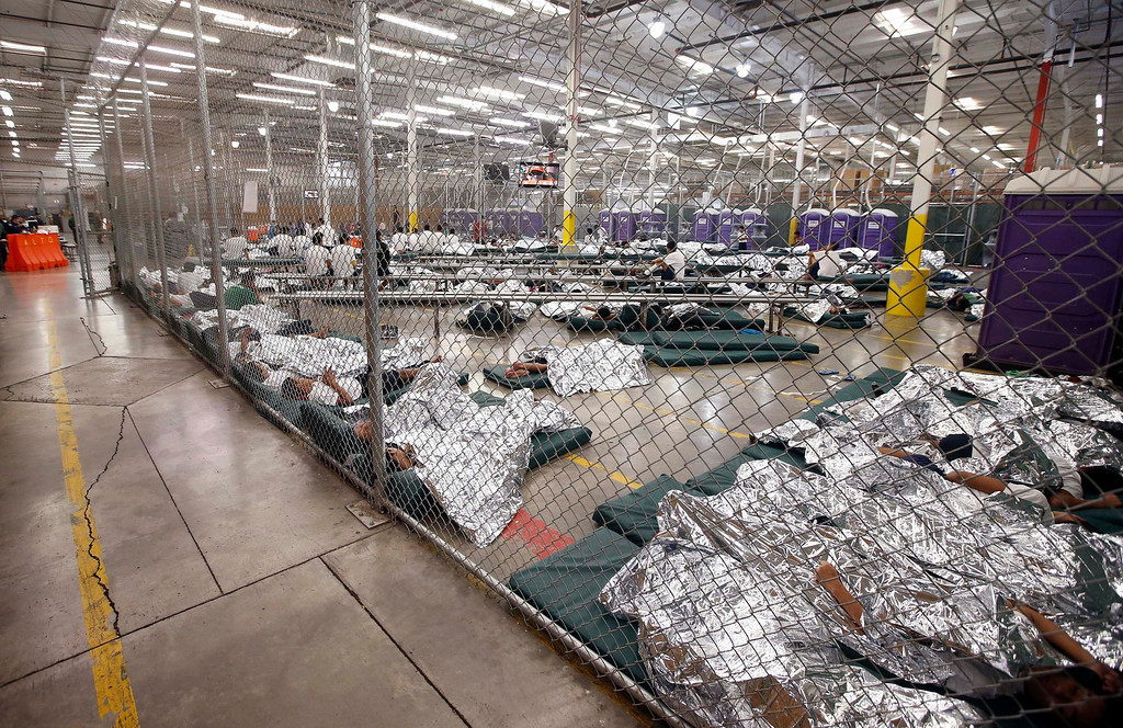 . Detainees sleep and watch television in a holding cell where hundreds of mostly Central American immigrant children are being processed and held at the U.S. (AP Photo/Ross D. Franklin, Pool)