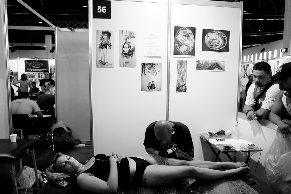 . A young woman has her leg tattooed by artist Anthony Orsatti of \'Skintastic\' during The Australian Tattoo & Body Art Expo at the Royal Hall of Industries, Moore Park on March 8, 2013 in Sydney, Australia. The annual three day event showcases some of Australia\'s best tattoo and body artists and is open to enthusiasts March 8-10.  (Photo by Lisa Maree Williams/Getty Images)