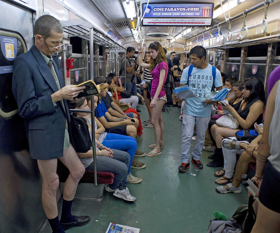 """. People taking part in the \""""No Pants Subway Ride\"""" remain on a metro train in Buenos Aires on January 12, 2014. \""""No Pants Subway Ride\"""" is an annual event in which transit passengers ride trains without wearing pants in January. The event is observed in dozens of cities worldwide. ALEJANDRO PAGNI/AFP/Getty Images"""