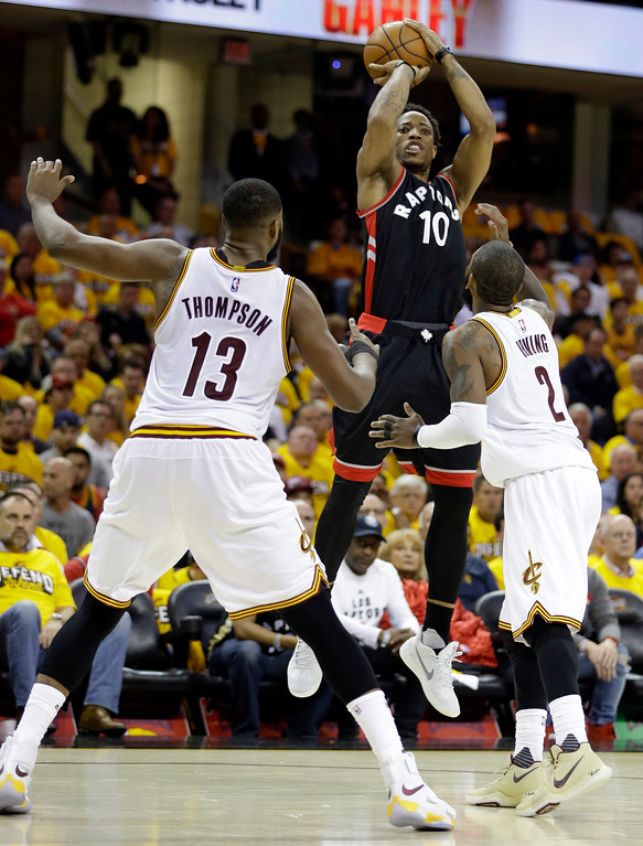 . Toronto Raptors\' DeMar DeRozan (10) shoots over Cleveland Cavaliers\' Tristan Thompson (13) and Kyrie Irving (2) in the first half in Game 1 of a second-round NBA basketball playoff series, Monday, May 1, 2017, in Cleveland. The Cavaliers won 116-105. (AP Photo/Tony Dejak)