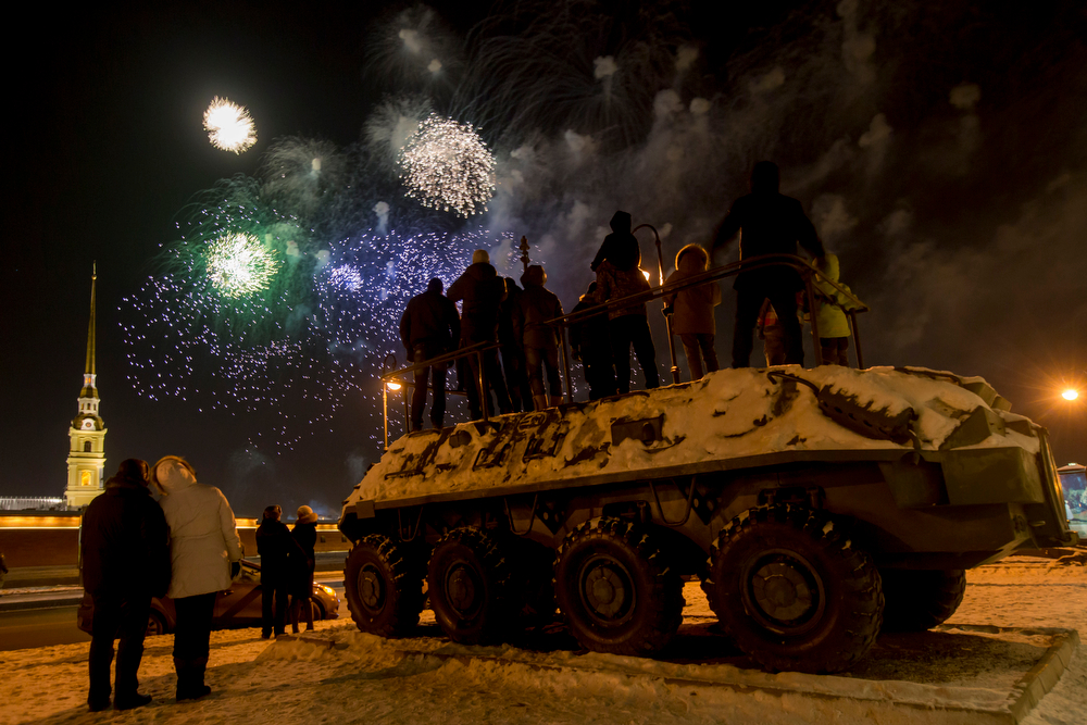 . People stand atop an armored personnel carrier displayed at a museum as they watch a fireworks display to mark the 70th anniversary of the battle that lifted the Siege of Leningrad in St. Petersburg, Russia, Monday, Jan. 27, 2014. The Nazi German and Finnish siege and blockade of Leningrad, now known as St. Petersburg, was broken on Jan. 18, 1943 but finally lifted Jan. 27, 1944. More than 1 million people died mainly from starvation during the 900-day siege. (AP Photo/Dmitry Lovetsky)