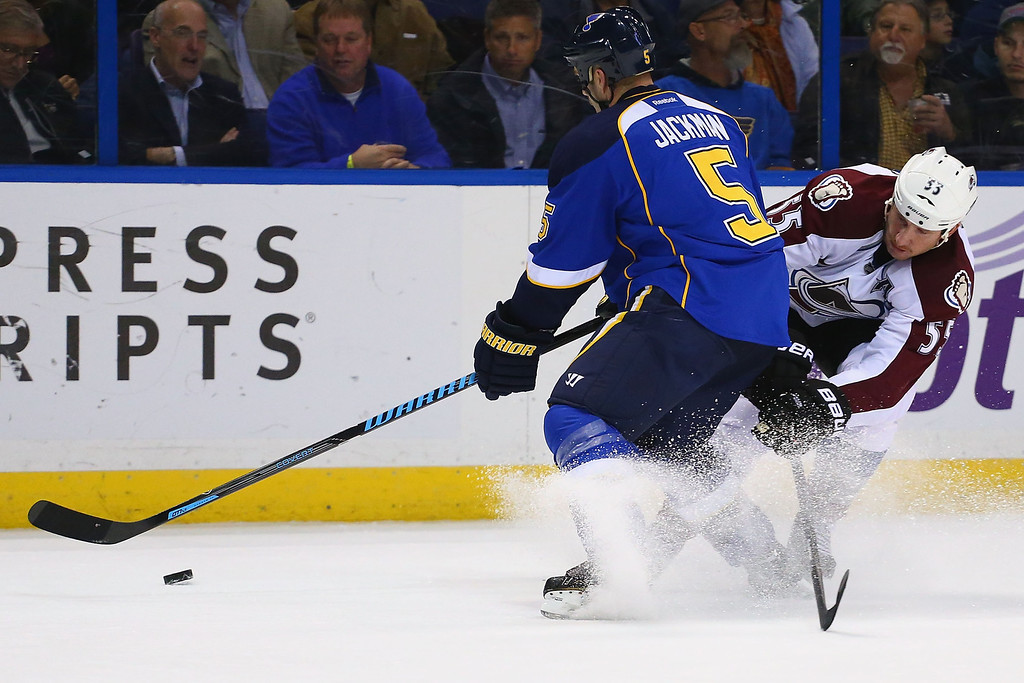 . ST. LOUIS, MO - NOVEMBER 14:  Barret Jackman #5 of the St. Louis Blues clears the puck against Cody McLeod #55 of the Colorado Avalanche at the Scottrade Center on November 14, 2013 in St. Louis, Missouri.  (Photo by Dilip Vishwanat/Getty Images)