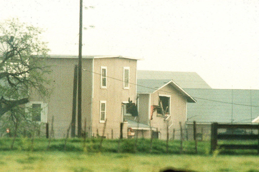 . Damage can be seen on the south end of the Branch Davidian compound after federal agents used an armored vehicle to punch gaping holes in the religious compound\'s buildings near Waco, Texas, on April 19, 1993. The FBI then fired tear gas canisters into the building where David Koresh and 95 followers had been holed-up for 51 days. (AP PKOTO/Ron Heflin)
