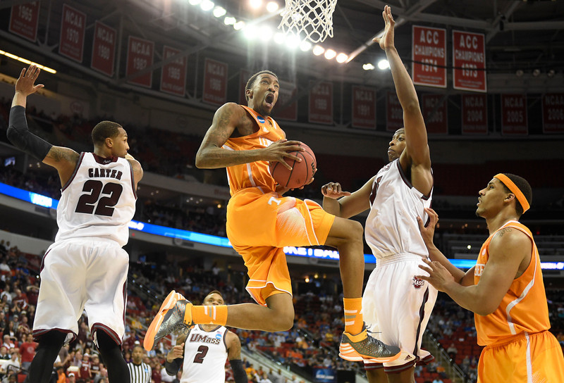 . Tennessee guard Jordan McRae (52), center, gets to the hoop in between Massachusetts forward Sampson Carter (22) and Massachusetts center Cady Lalanne (25), while Tennessee forward Jarnell Stokes, right, looks on during the second half of an NCAA college basketball tournament game at the PNC Arena in Raleigh, N.C. on Friday, March 21, 2014. Tennessee won 86-67. (AP Photo/Knoxville News Sentinel, Adam Lau)