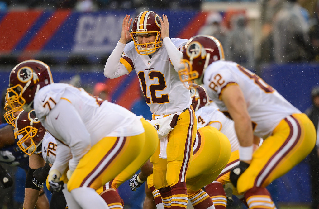 . Quarterback Kirk Cousins #12 of the Washington Redskins stands at the line of scrimmage against the New York Giants in the first half  at MetLife Stadium on December 29, 2013 in East Rutherford, New Jersey. (Photo by Ron Antonelli/Getty Images)