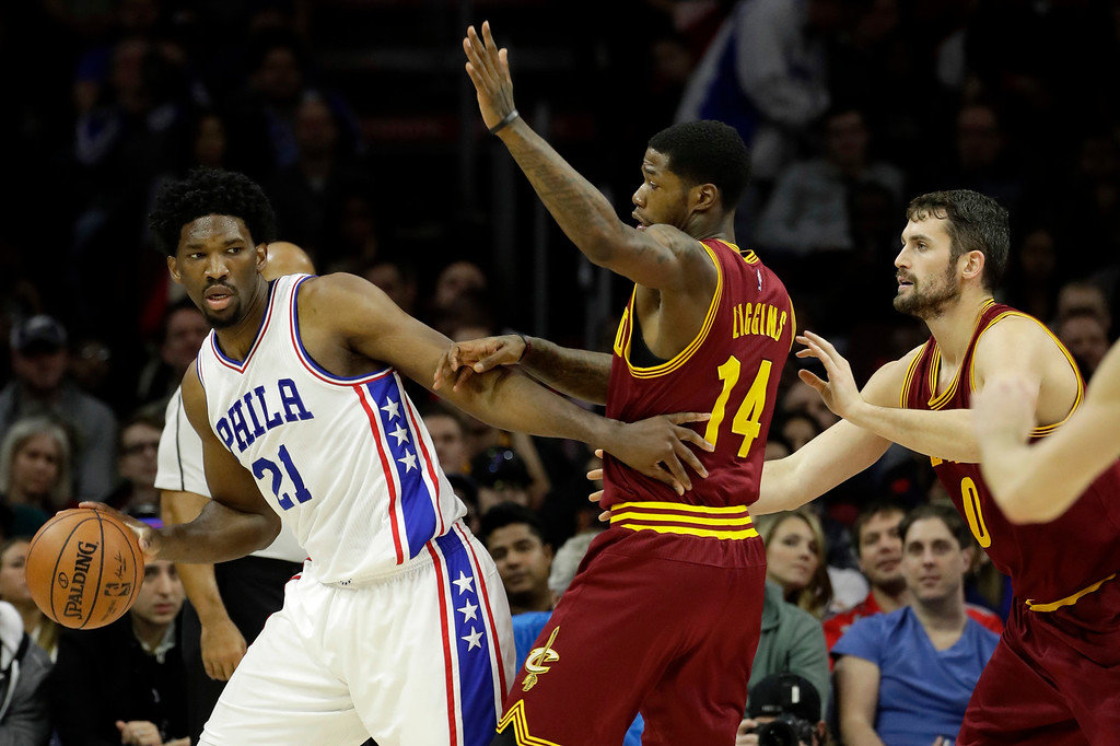 . Philadelphia 76ers\' Joel Embiid, left, tries to get around Cleveland Cavaliers\' DeAndre Liggins, center, and Kevin Love during the first half of an NBA basketball game, Sunday, Nov. 27, 2016, in Philadelphia. (AP Photo/Matt Slocum)