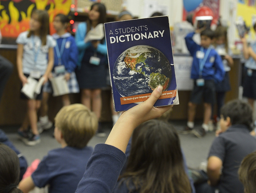 """. LONG BEACH, CALIF. USA -- A third grader raises their dictionaries to answer a question during a game at the El Dorado Beach Library in Long Beach, Calif., on February 28, 2013. This is the 10th. year that dictionaries have been purchased and distributed to third-grade students in the Long Beach Unified School District, charter, local parochial and private schools. The Long Beach Dictionary Project promotes literacy and the goal that all students will leave third-grade at the end of the year as \""""good writers, active readers, and creative thinkers\"""". The Miller Foundation, which has been providing dictionaries to third-graders since 2003, is celebrating giving away its 100,000 lexicon literary.  Photo by Jeff Gritchen / Los Angeles Newspaper Group"""