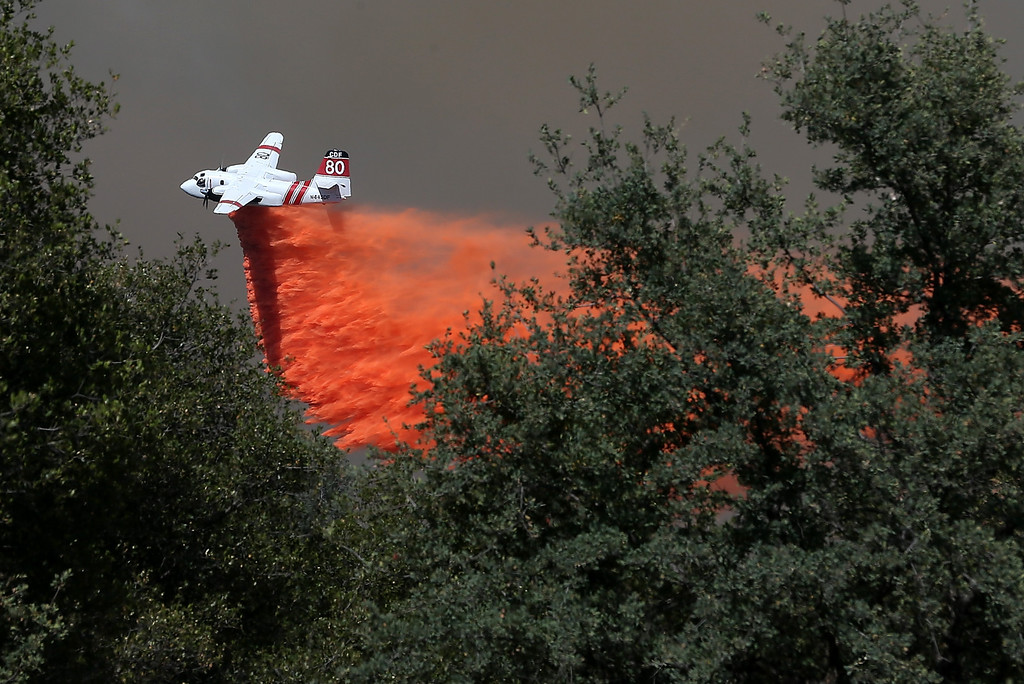 . GROVELAND, CA - AUGUST 22:  A California Department of Forestry air tanker drops fire retardant on a ridge ahead of the advancing Rim Fire on August 22, 2013 in Groveland, California. The Rim Fire continues to burn out of control and threatens 2,500 homes outside of Yosemite National Park. Over 1,000 firefighters are battling the blaze that was reduced to only 2 percent containment after it nearly tripled in size overnight.  (Photo by Justin Sullivan/Getty Images)
