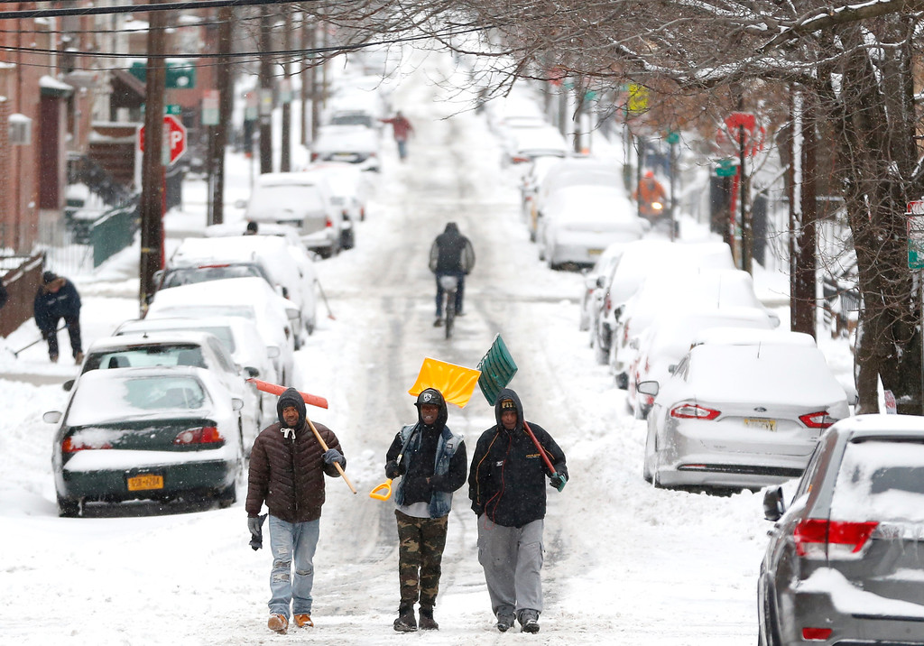 . Men carry shovels as they walk on a snow covered road after an overnight snowstorm, Tuesday, Jan. 27, 2015, in Hoboken, N.J.  New Jersey starting digging out, roads reopened and mass transit started working to get back on schedule Tuesday as a winter storm that was predicted to bring several feet of snow to parts of the state fell short of predictions. (AP Photo/Julio Cortez)