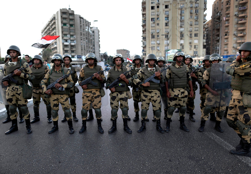 . Military special forces surround supporters of Islamist leader Mohammed Morsi in Nasser City, Cairo, Egypt, Wednesday, July 3, 2013. Army troops backed by armor and including commandos have deployed across much of the Egyptian capital, near protest sites and at key facilities and major intersections. The deployment is part of a bid by the military to tighten its control of key institutions Wednesday, slapping a travel ban on embattled president Mohammed Morsi and top allies in preparation for an almost certain push to remove the Islamist president with the expiration of an afternoon deadline.  (AP Photo/Hassan Ammar)