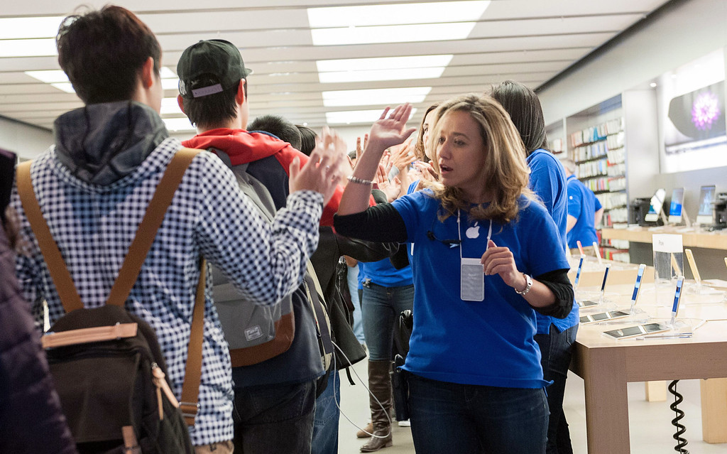 . Customers high-five an Apple employee as they go to buy the new iPhone 6 at the Eaton Centre in Toronto, Ont. on Friday, Sept. 19, 2014.  (AP Photo/The Canadian Press,Hannah Yoon)