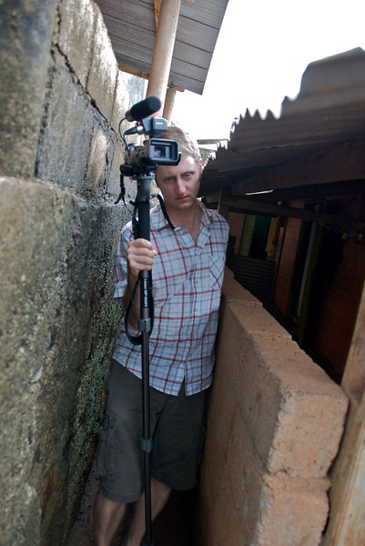 Andy walks through an alley with his camera  OFM team