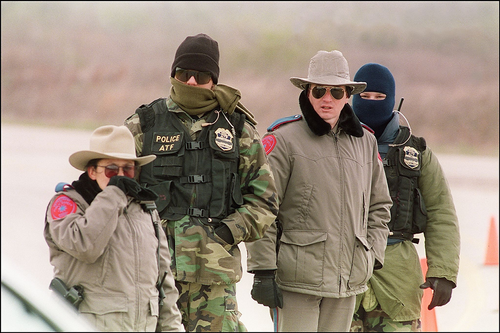 Description of . Agents of the Bureau of Alcohol, Tobacco and Firearms and local Texan authorities bundle up against cold temperatures as the vigil outside the Branch Davidian compound continued for the thirteenth day on March 12, 1993. After a shootout in Waco in 1993 that killed four federal agents and six members of the Branch Davidian religious sect, authorities negotiated with cult leader David Koresh for 51 days. On the final day, April 19, 1993, a few hours after a government tank rammed the cult's wooden fortress, the siege ended in a fiery blaze, killing Koresh and 80 of his followers.  Authorities later learned that leader David Koresh had renamed the compound Ranch Apocalypse and prophesied that the end of days from the Bible's Book of Revelations would begin there. BOB STRONG/AFP/Getty Images