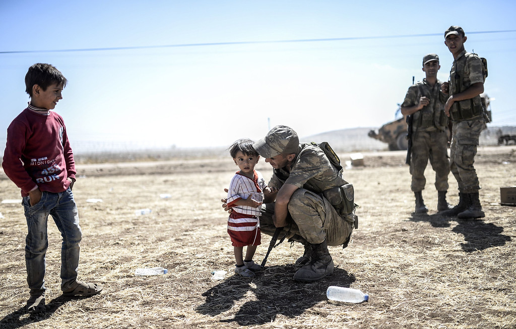 ". A Turkish soldier kisses Syrian Kurds children in Sanliurfa province, on September 20, 2014, after they crossed the border between Syria and Turkey near the southeastern town of Suruc. Several thousand Syrian Kurds began crossing into Turkey on September 19 fleeing Islamic State fighters who advanced into their villages, prompting warnings of massacres from Kurdish leaders. Turkey on September 19 reopened its border with Syria to Kurds fleeing Islamic State (IS) militants, saying a ""worst-case scenario\"" could drive as many as 100,000 more refugees into the country.   BULENT KILIC/AFP/Getty Images"
