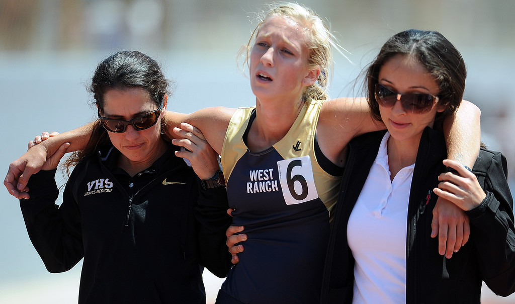 . West Ranch\'s Taylor Welker is helped off the track after collapsing after the 1600 meters race during the CIF-SS track & Field championship finals in Hilmer Stadium on the campus of Mt. San Antonio College on Saturday, May 18, 2013 in Walnut, Calif.  (Keith Birmingham Pasadena Star-News)