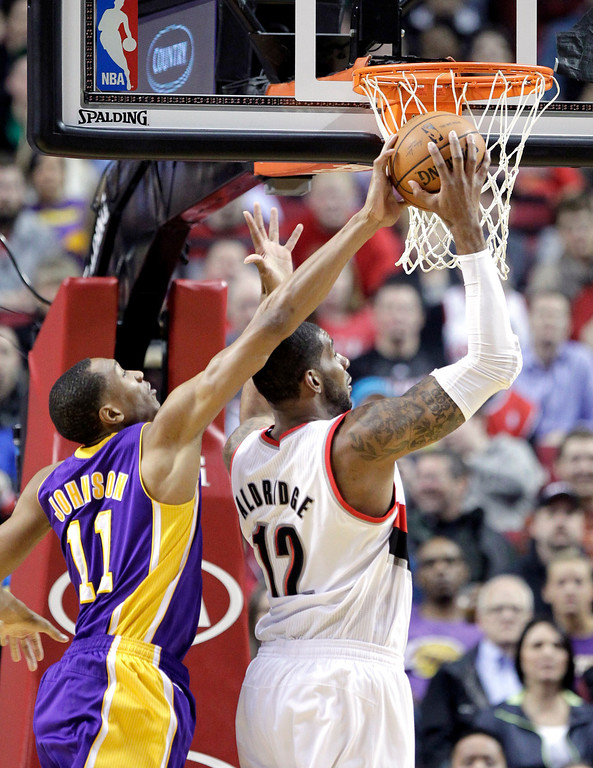 . Los Angeles Lakers forward Wesley Johnson, left, blocks a shot attempt by Portland Trail Blazers forward LaMarcus Aldridge during the first half of an NBA basketball game in Portland, Ore., Monday, March 3, 2014. (AP Photo/Don Ryan)